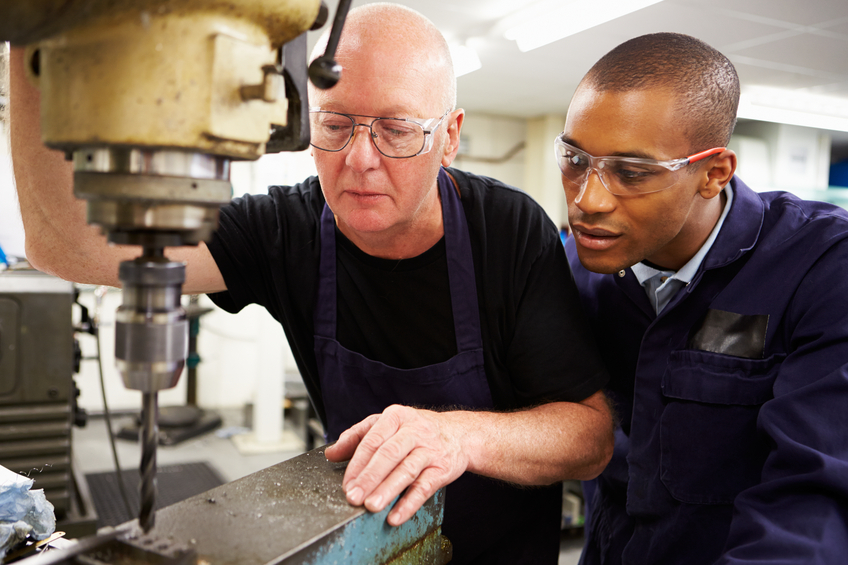 Engineer Teaching Apprentice To Use Milling Machine Together